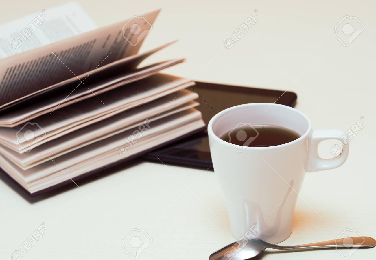 Scrivania In Legno Chiaro : Tazza bianca di tè tavoletta digitale e cucchiaio sulla scrivania