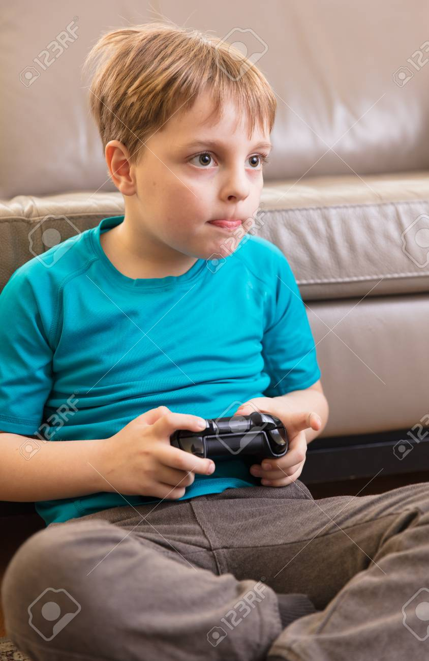Banque Dimages Little Boy Playing Some Video Games At Home Using A Controller Making Different Expressions