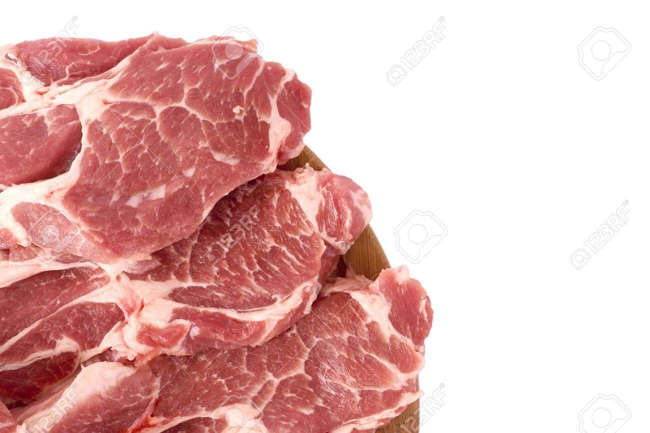 Raw and fresh sliced pork meat laid out on a wooden round board, isolated on white background. Top view. - 156775358