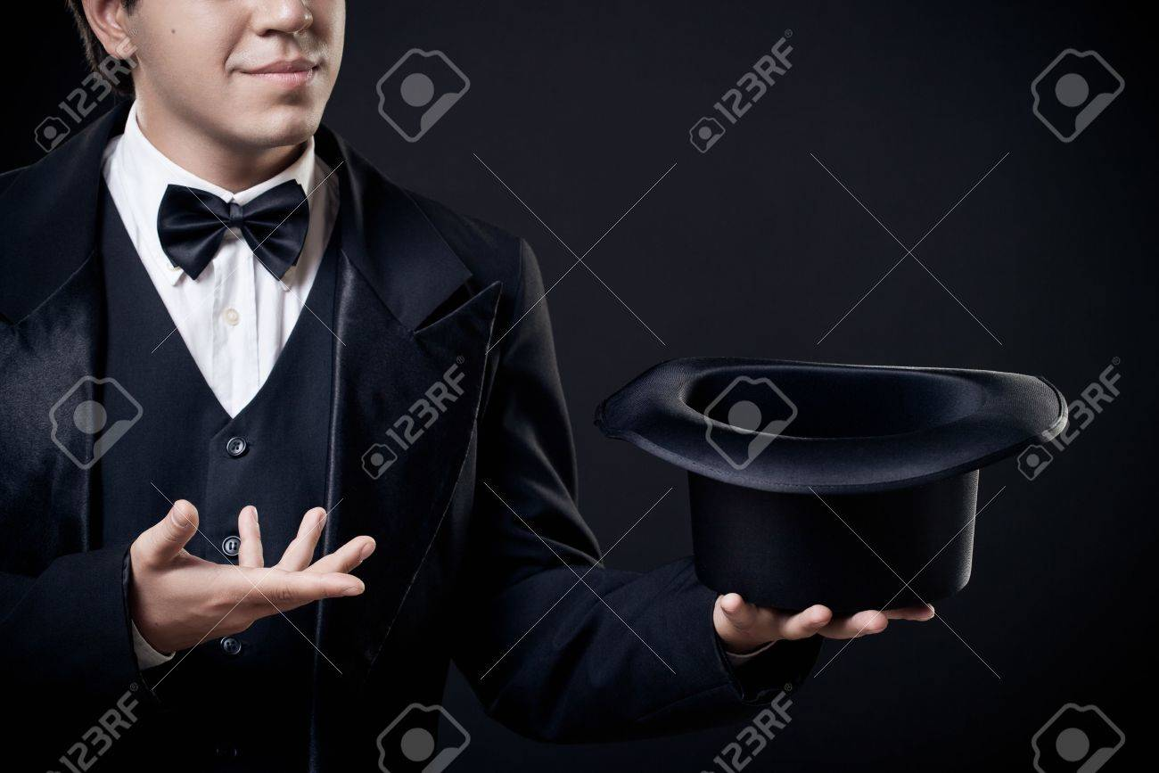 closeup of magician showing tricks with top hat isolated on dark background Stock Photo - 14890792