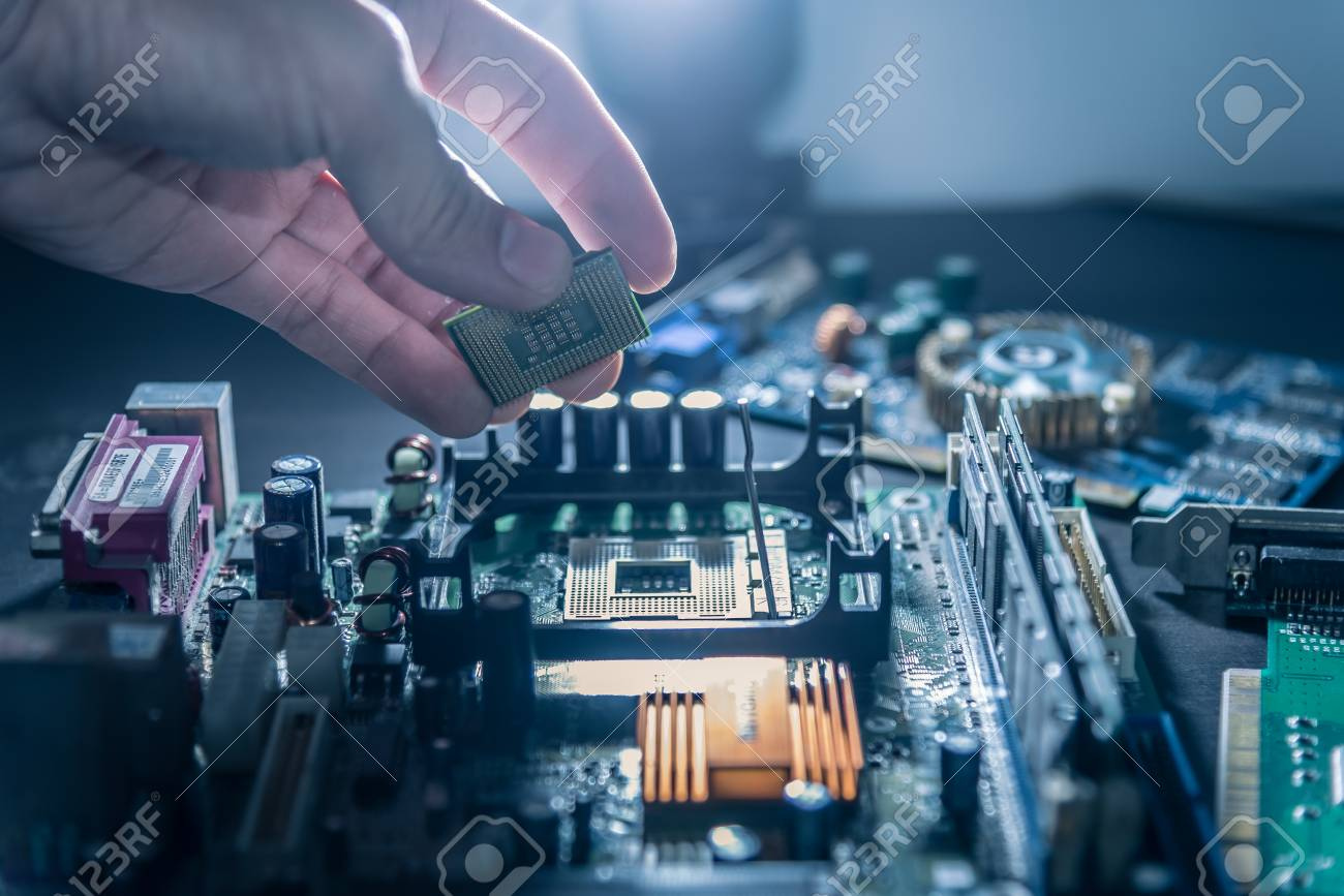 The technician is putting the CPU on the socket of the computer motherboard. - 93717860