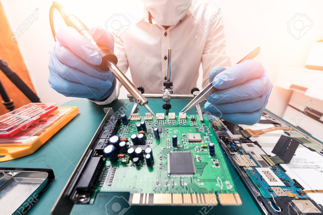 The asian technician repairing the motherboard by soldering in the lab. the concept of computer hardware, mobile phone, electronic, repairing, upgrade and technology. - 101445213