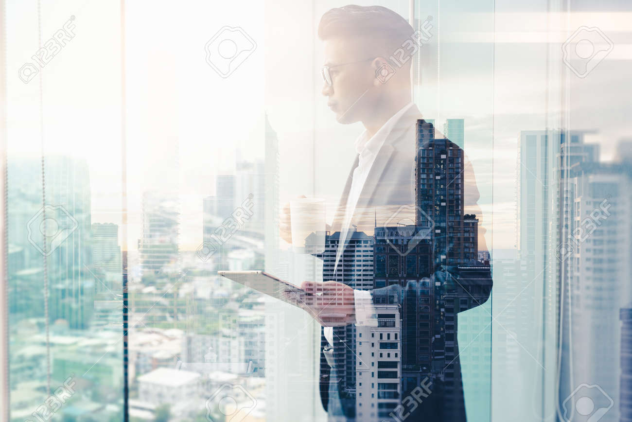 The double exposure image of the businessman using a taplet in the office. The concept of modern life, business, city life and internet of things. - 155504706