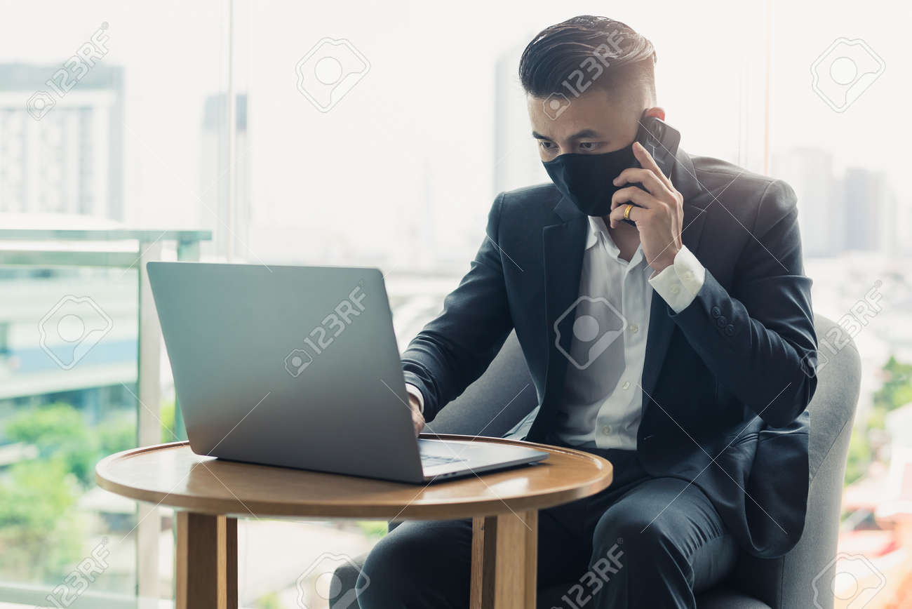 the businessman wearing a protective face mask and working during the coronavirus pandemic. the concept of coronavirus, pandemic, entrepreneur and business. - 155917857