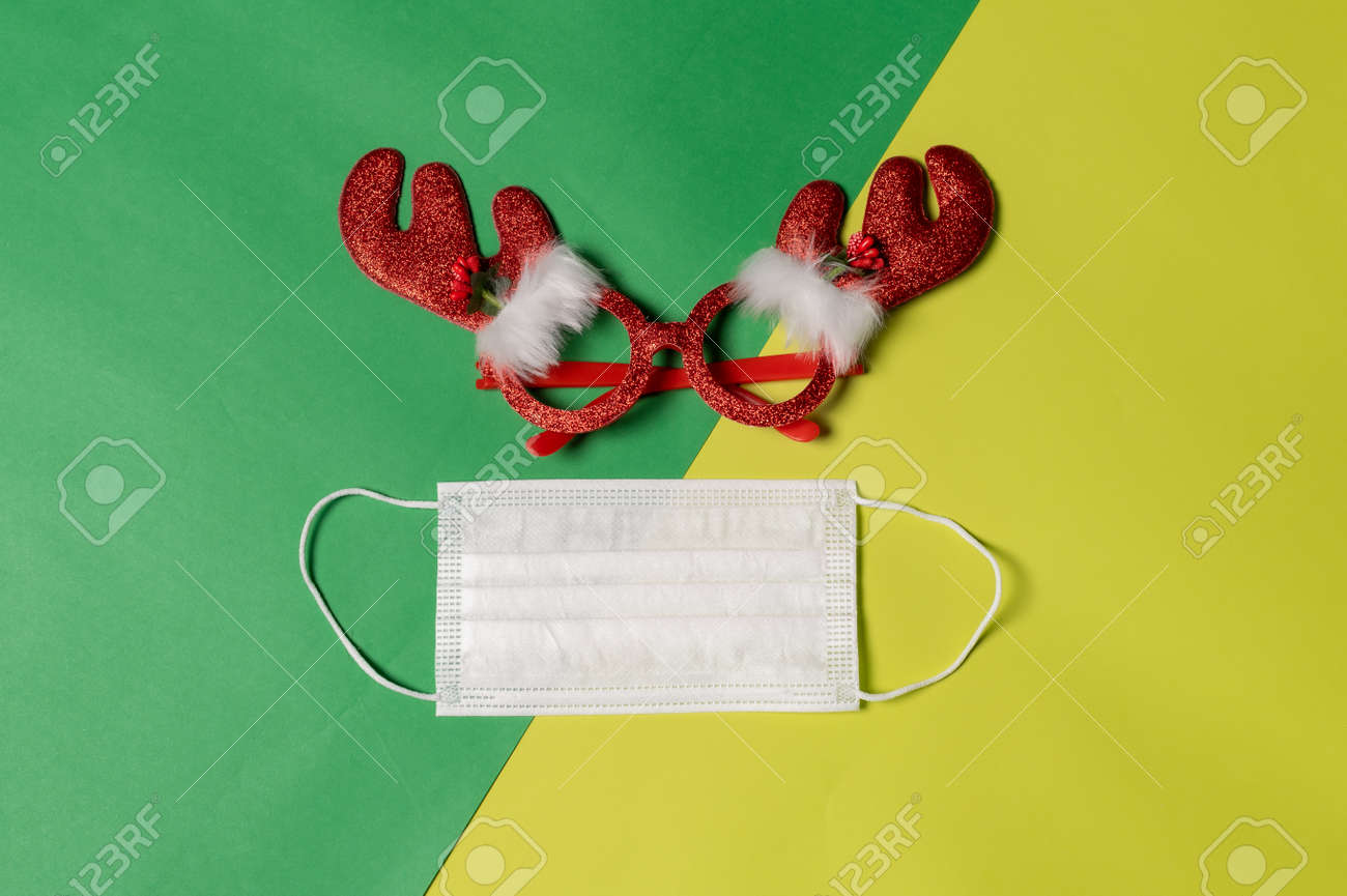 the Christmas props and the protective mask laying on the color backdrop. the concept of festival, pandemic, celebrating, coronavirus and Christmas - 159293582