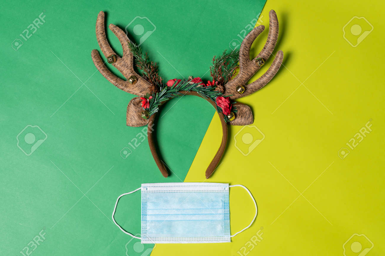 the Christmas props and the protective mask laying on the color backdrop. the concept of festival, pandemic, celebrating, coronavirus and Christmas - 159293597