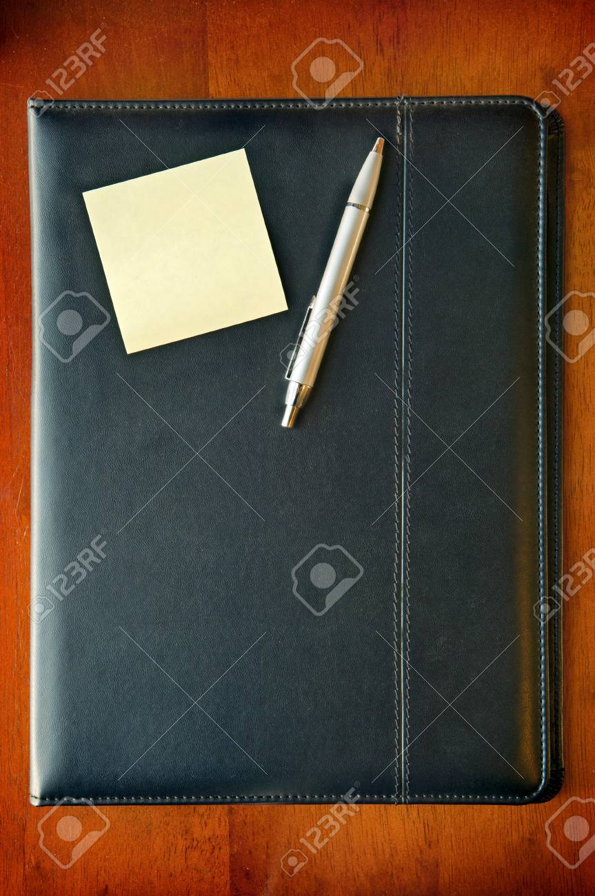 A black executive folder on timber desk with sticky note and silver pen Stock Photo - 8235159