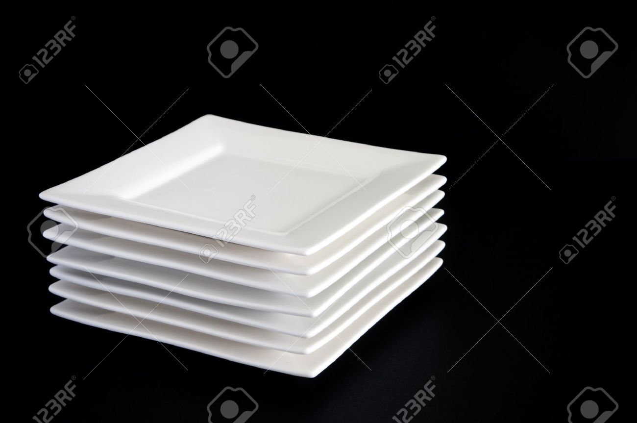contemporary square white plates stacked against a dark black  - contemporary square white plates stacked against a dark black backgroundstock photo