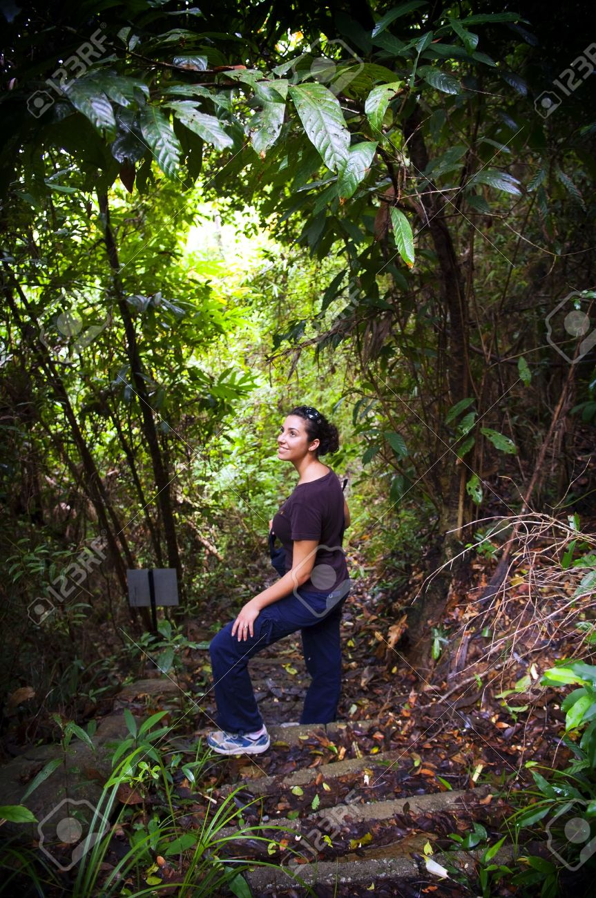 An active young woman hiking in thick jungle Stock Photo - 10042898