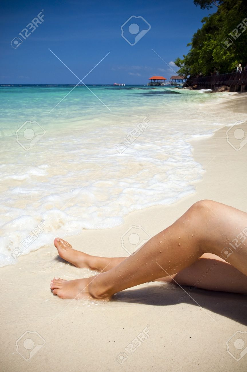 Womans legs on beautiful tropical beach with bright sand Stock Photo - 10042905