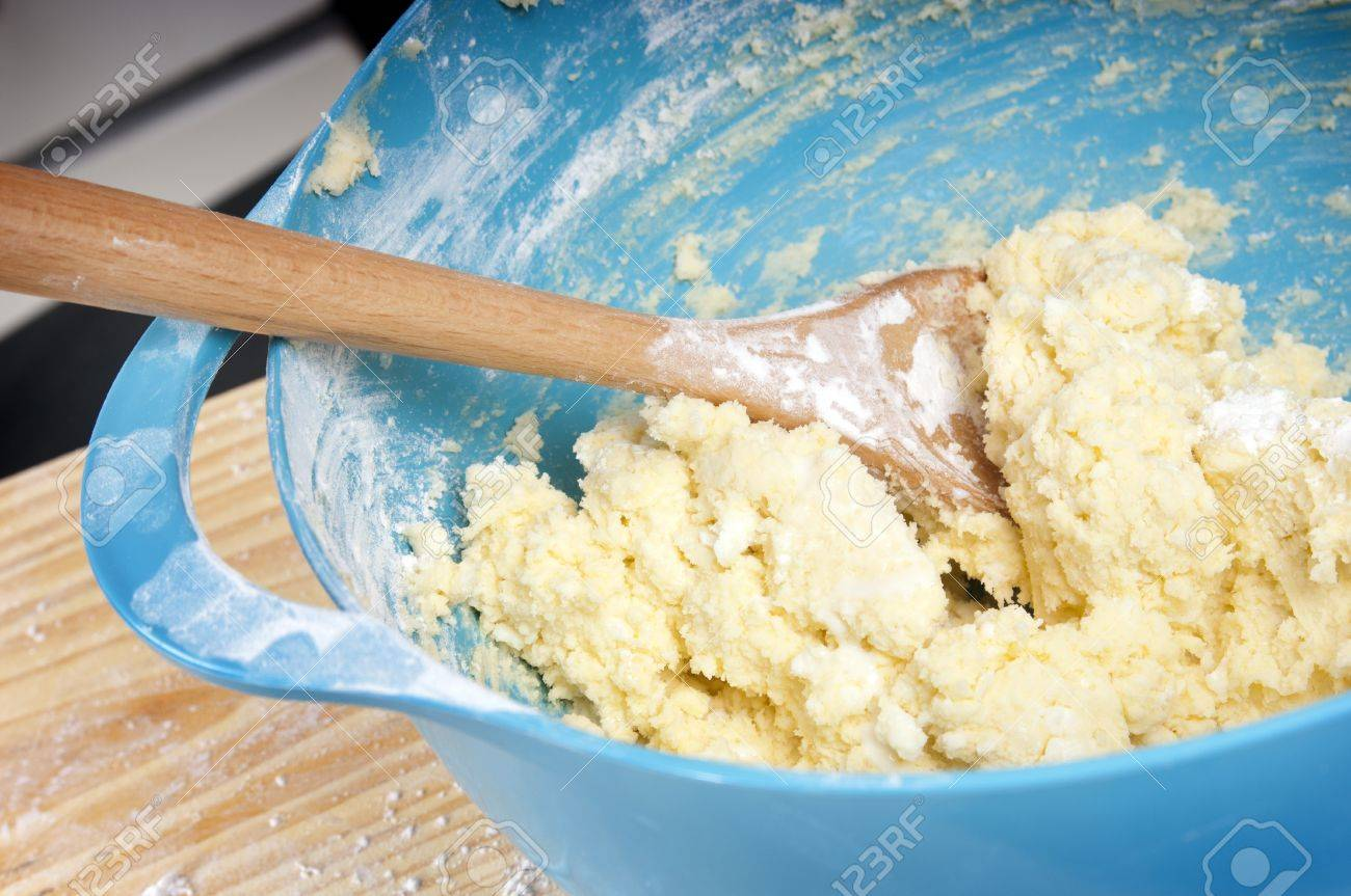A blue mixing bowl with mixture and wooden spoon Stock Photo - 10842794