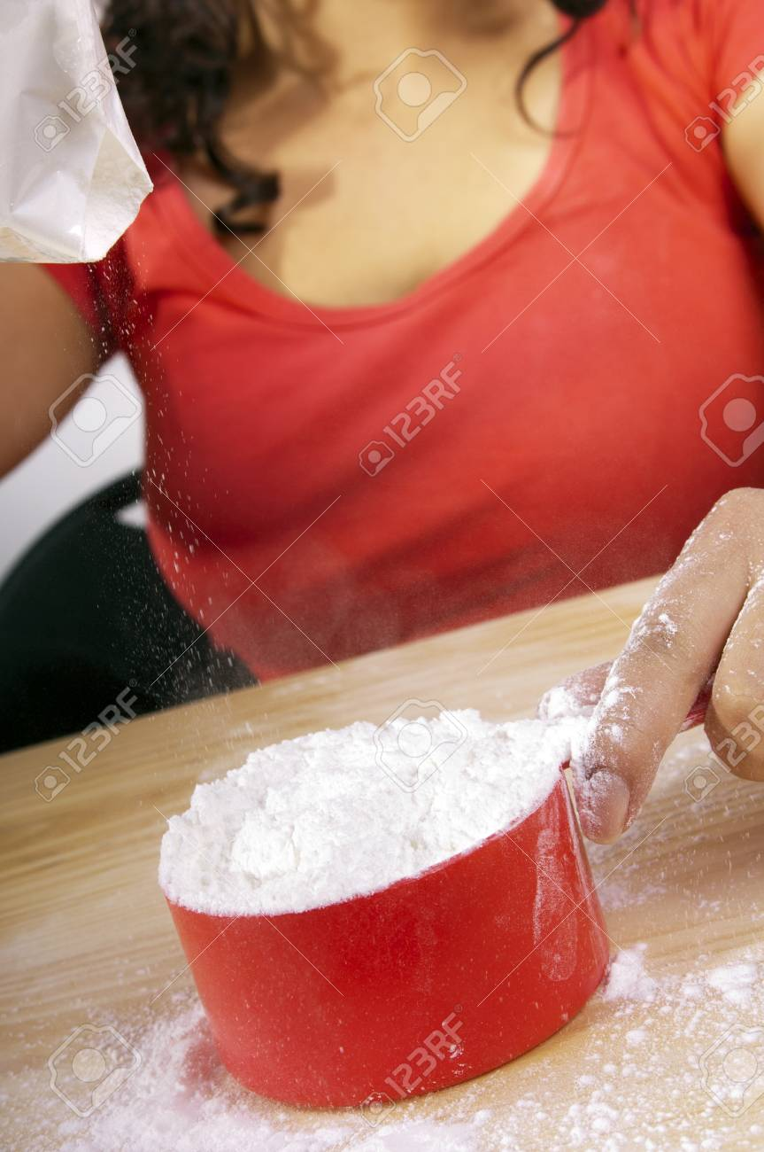 A woman pours flour into a measuring cup while baking Stock Photo - 10842793
