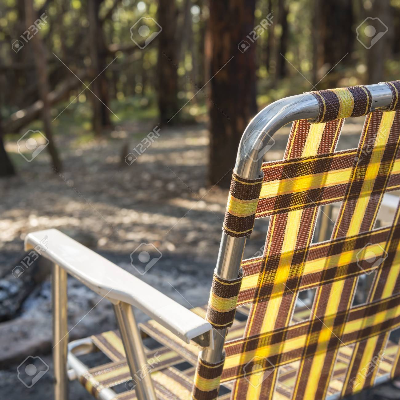 Retro Fold Up Camping Chair In Front Of The Fire Woods Stock Photo