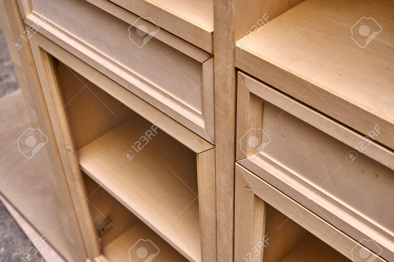 Beautiful professionally made wood cabinet in process of production in workshop. Wardrobe with drawers. Furniture manufacture. Close-up - 120652326