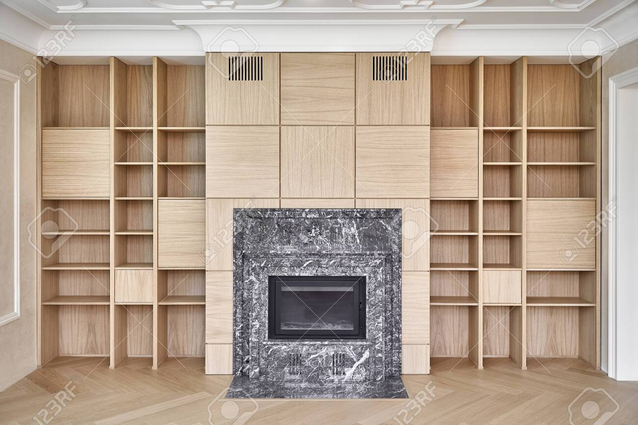 Wooden bookshelves. Wooden shelving around the fireplace. Furniture manufacture. Close-up - 147776019