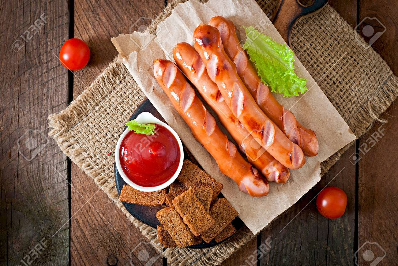Grilled sausages, crackers and beer on a wooden background in rustic style - 39128794