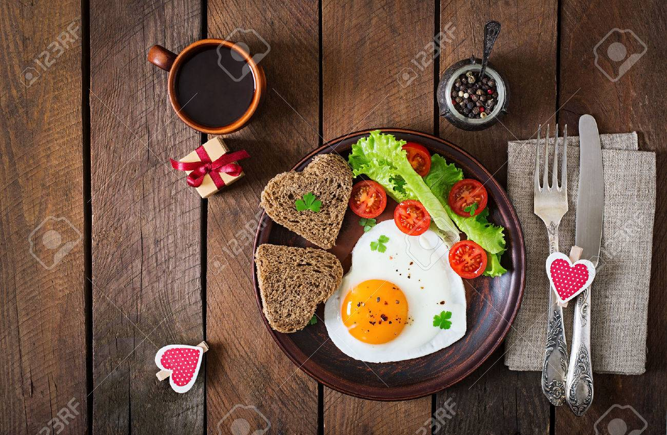Breakfast on Valentine's Day - fried eggs and bread in the shape of a heart and fresh vegetables. Top view - 50363404