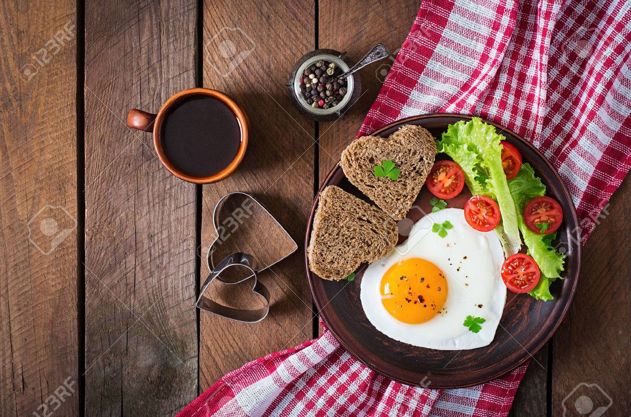 Breakfast on Valentine's Day - fried eggs and bread in the shape of a heart and fresh vegetables. Top view - 50363441