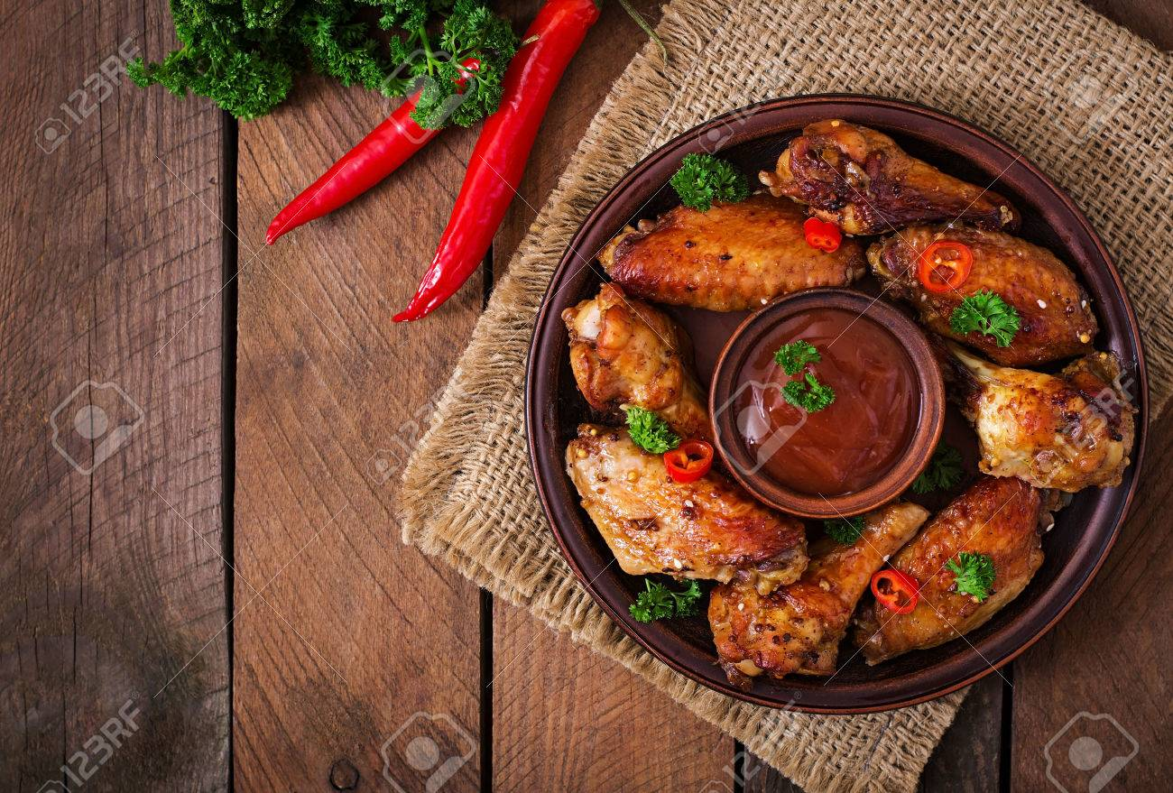 Sour-sweet baked chicken wings and sauce.Top view - 52913591