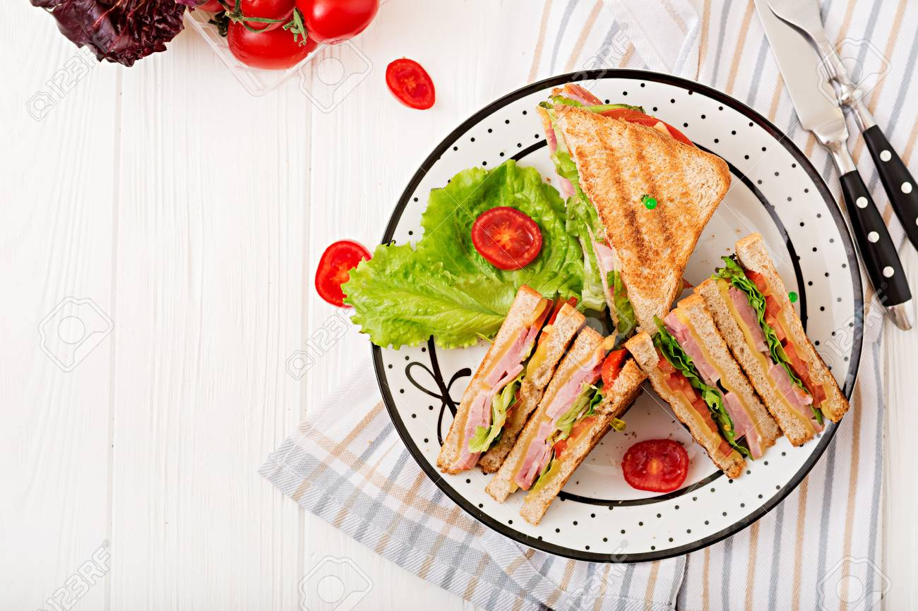 Club sandwich - panini with ham, cheese, tomato and herbs. Top view - 91018646