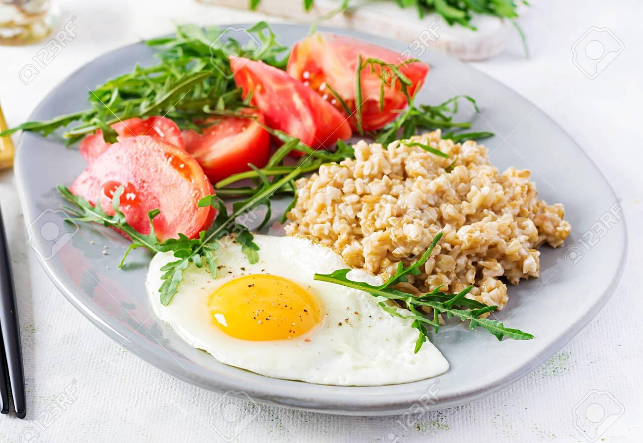 Breakfast oatmeal porridge with fried egg, tomatoes, arugula. Healthy food. - 151895964