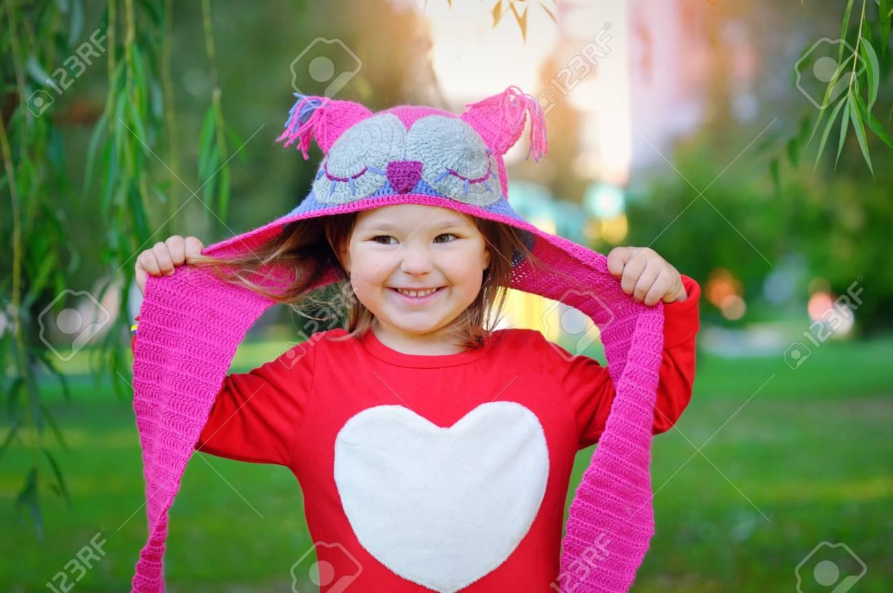 Banque d images - Belle petite fille en riant bébé dans un manteau rouge et  coloré bonnet tricoté et écharpe jouer avec érable feuilles jaunes dans un  parc ... 21ff48d83da