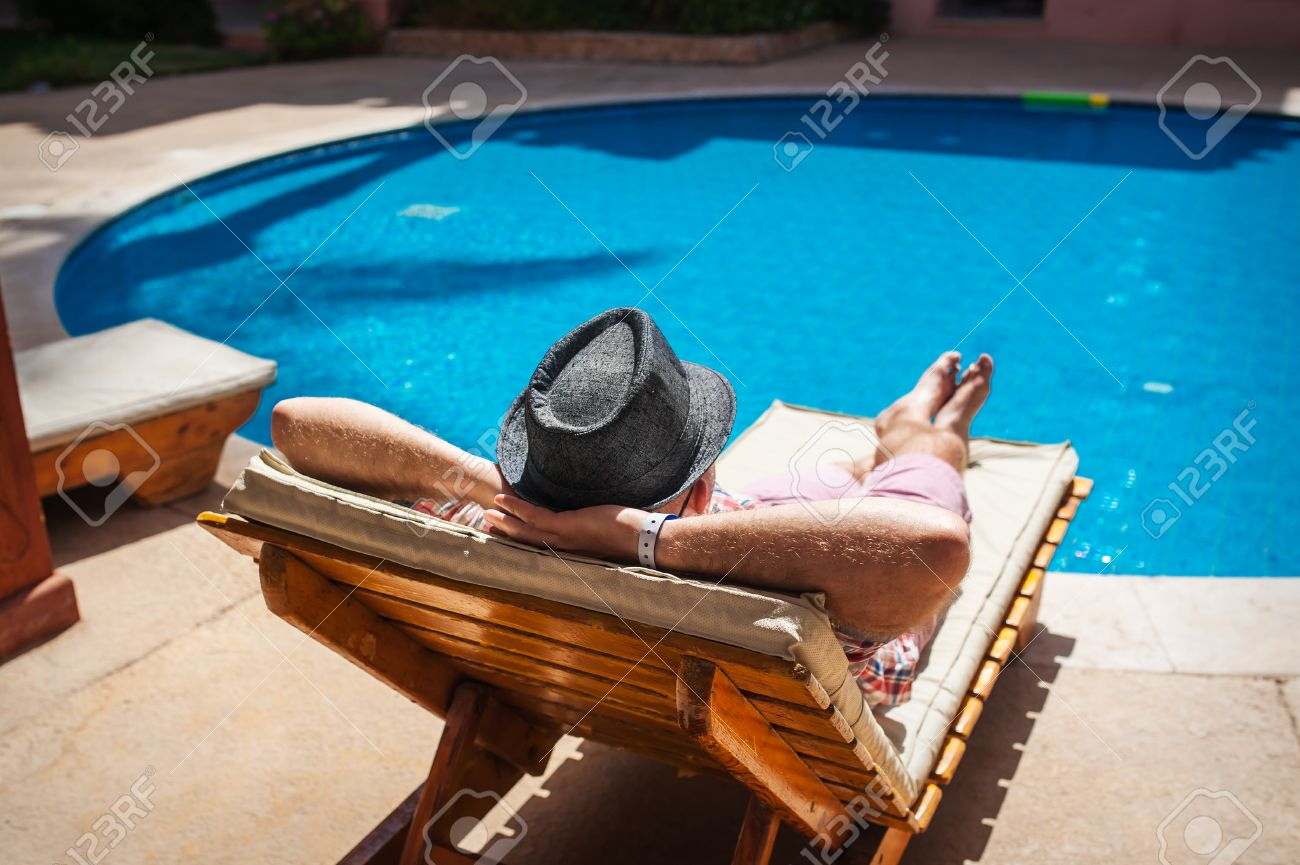 banque dimages lhomme dans un chapeau allong sur un transat prs de la piscine - Transat Piscine