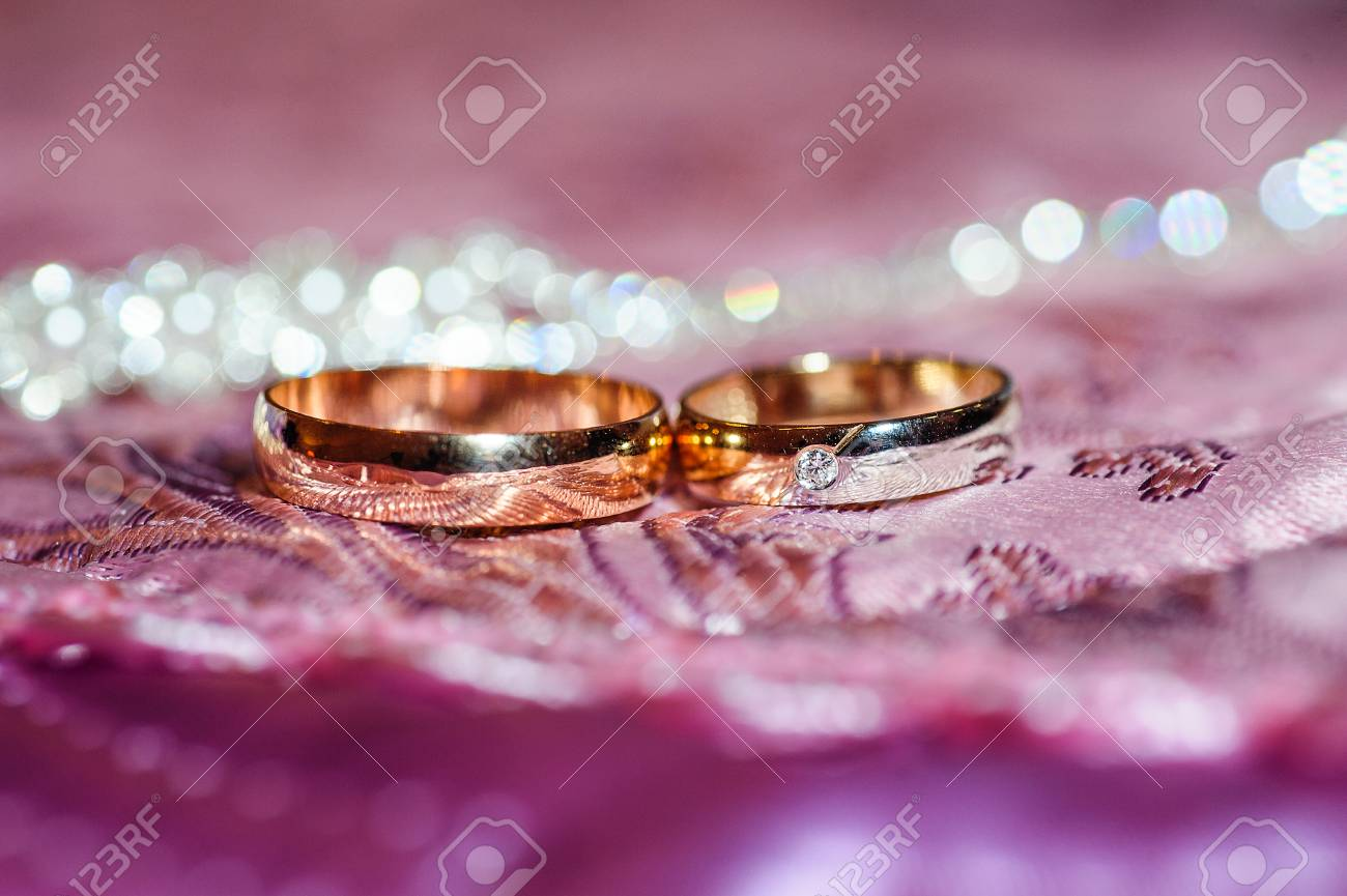 Two Gold Wedding Rings Lie On A Pillow Close Up Stock Photo, Picture ...