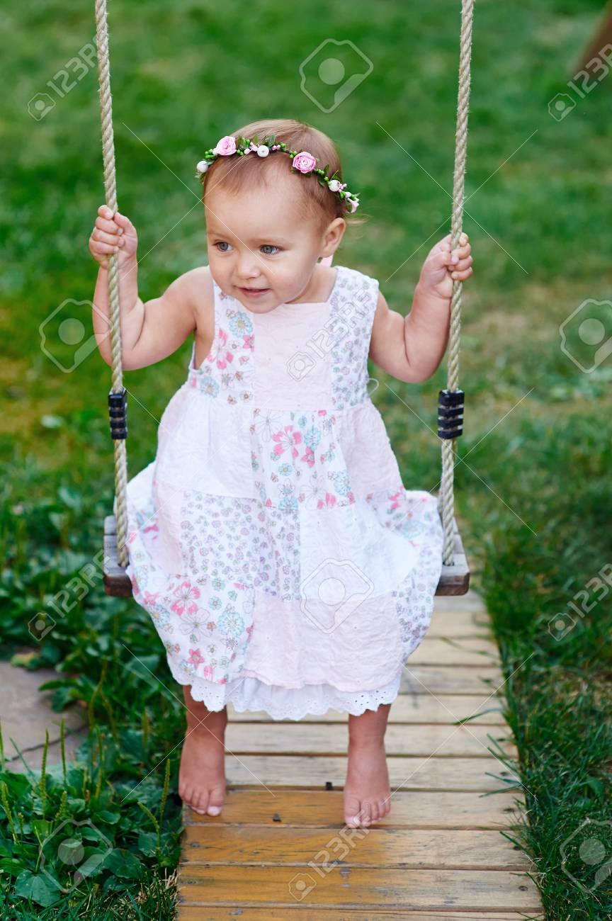 adorable baby girl wearing a white dress enjoying a swing ride