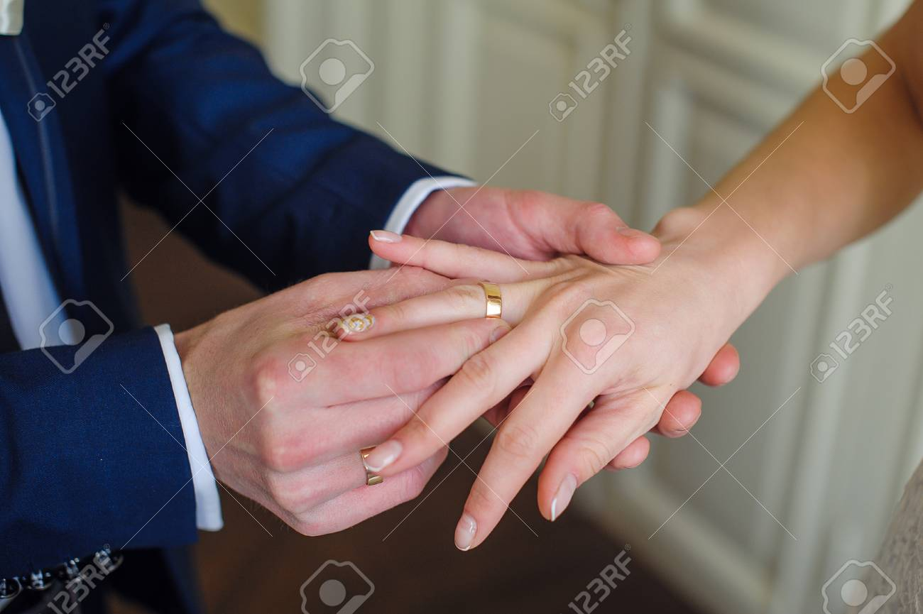 Groom Wears Bride A Gold Ring On Her Finger. Stock Photo, Picture ...