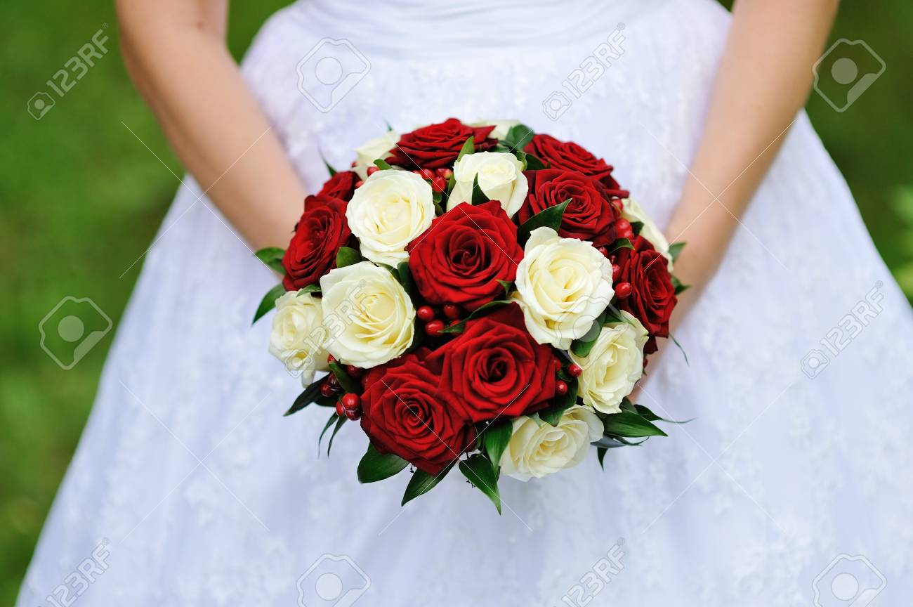 Red And White Wedding Bouquet Of Roses In The Hands Of The Bride