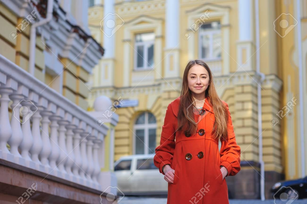 best service 25088 d2754 Giovane donna in cappotto arancione posa nella città vecchia