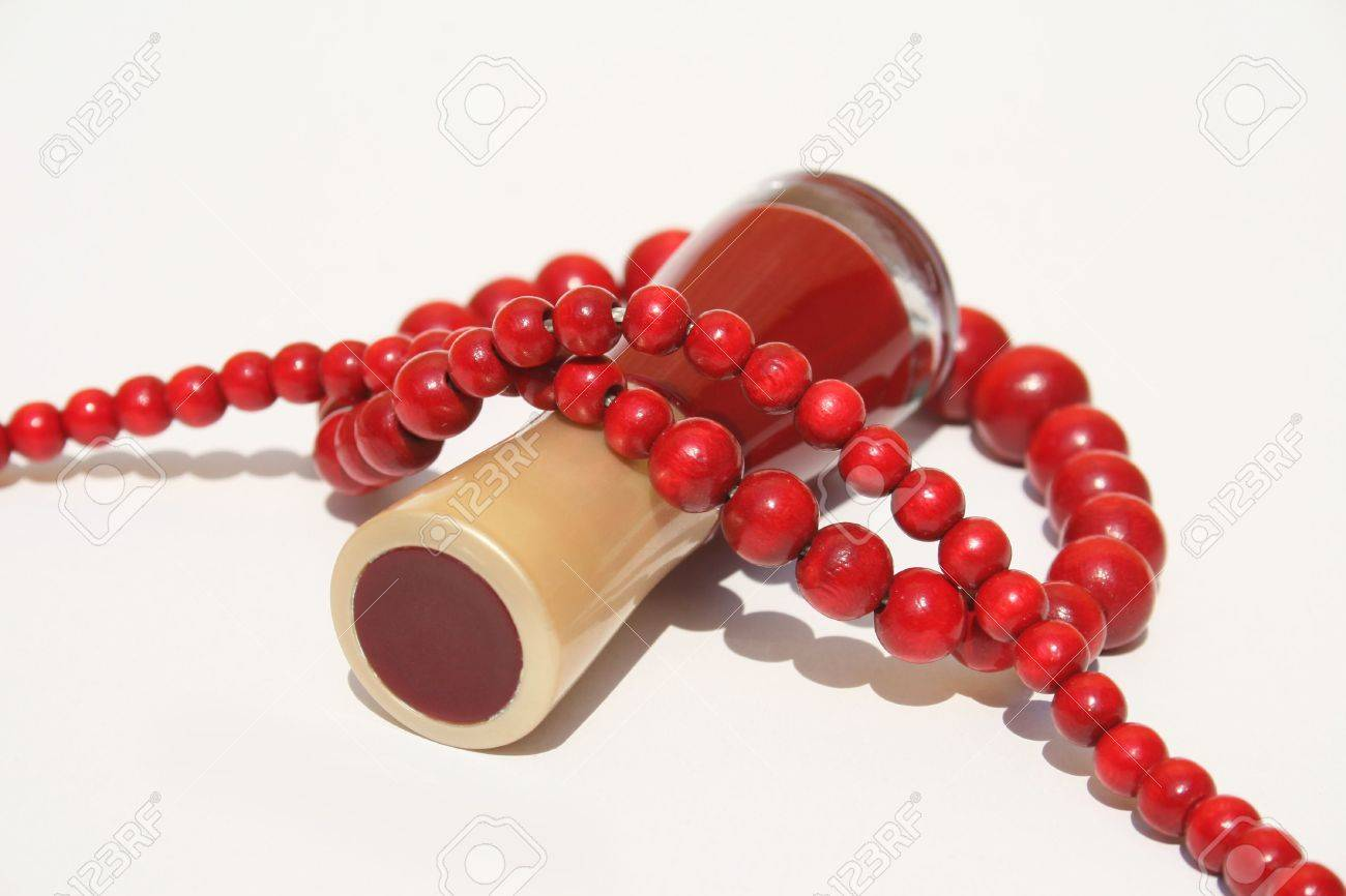 A bottle of red fingernail polish on side with strand of red wooden beaded necklace wrapped around Stock Photo - 3312837