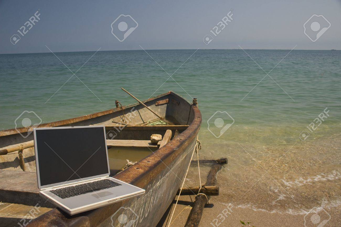 laptop sitting on side of small fishing boat that is docked on