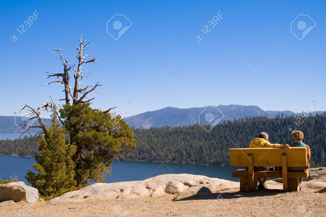 A couple relaxing on bench overlooking a view of mountain lake Stock Photo - 3934522