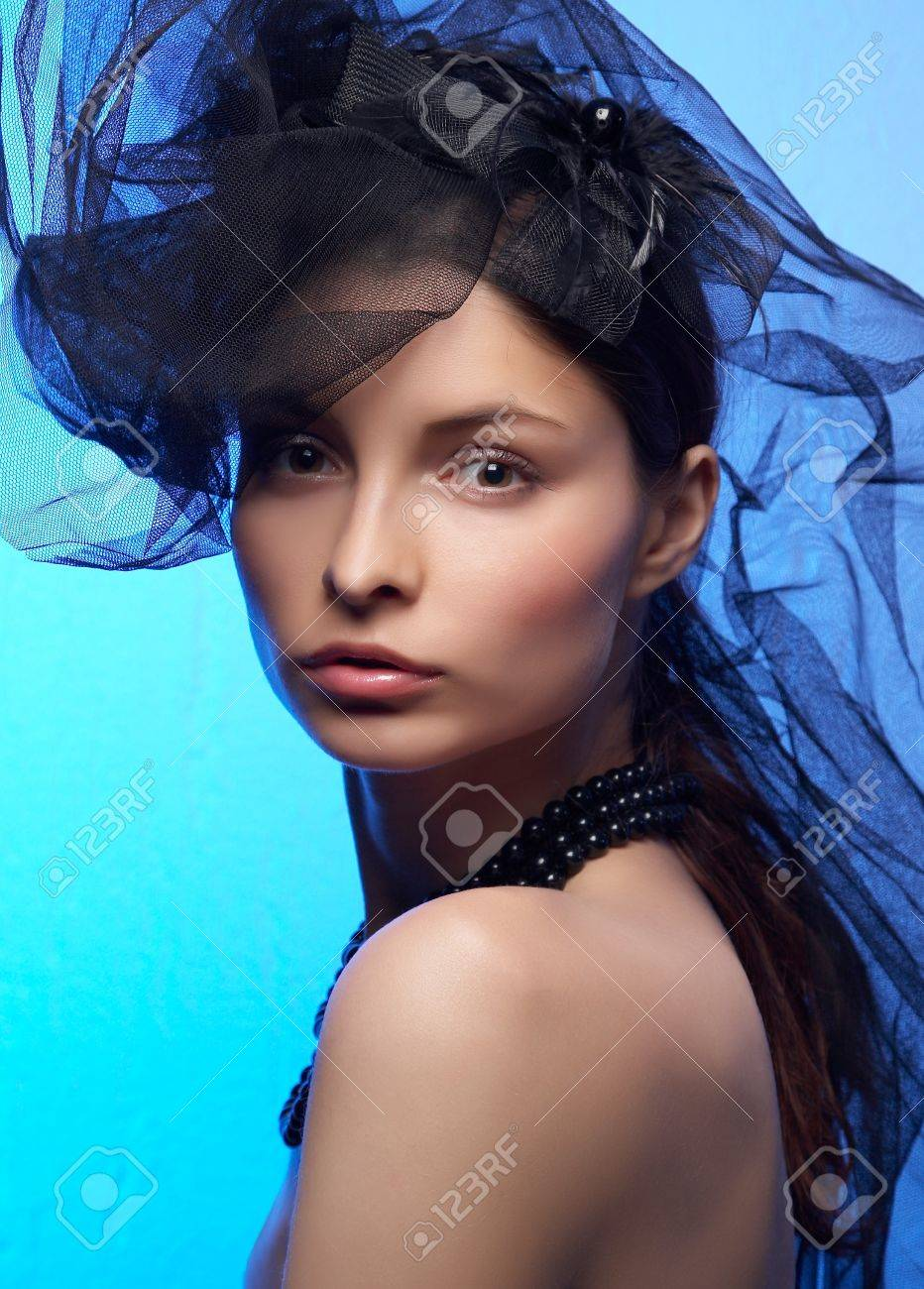 Young beautiful woman in black hat on the blue background Stock Photo - 3960159