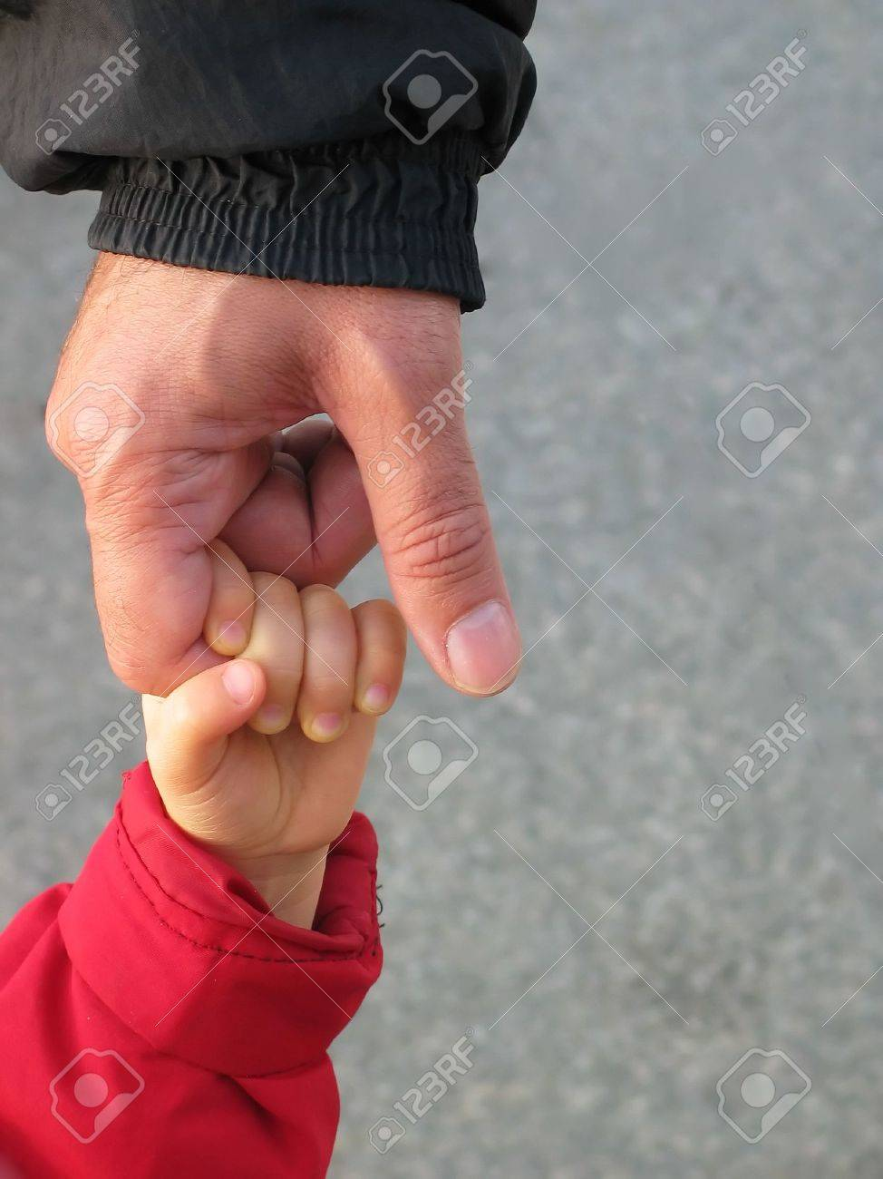 baby reaching up to hold on to father's finger, with space for text on the right side Stock Photo - 711512