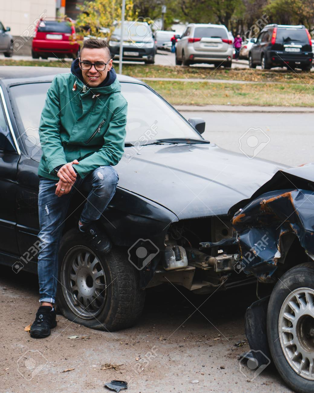 Man In Glasses And Jacket Is Smiling At A Two Wrecked Cars Stock Photo,  Picture And Royalty Free Image. Image 109945098.