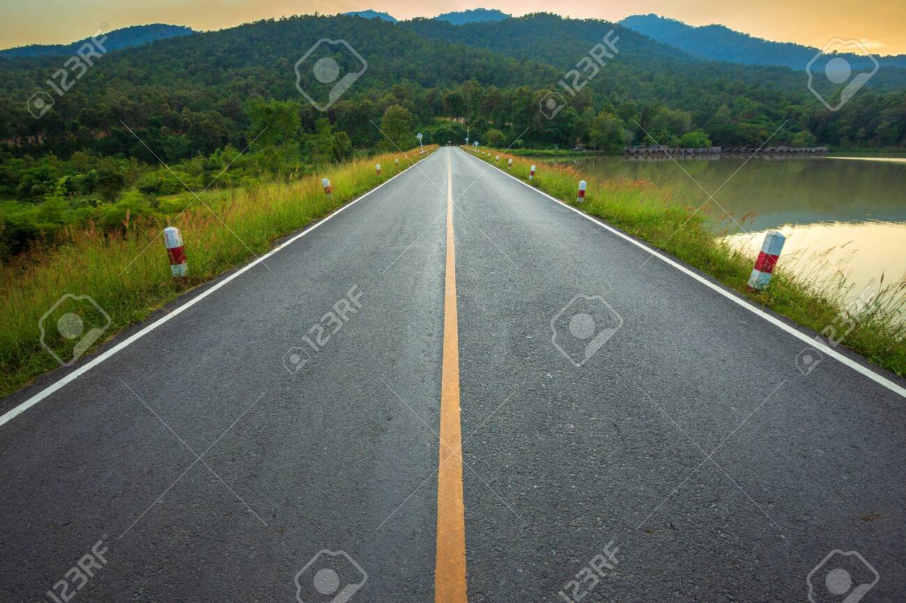 Rural road with Scenic view of the reservoir Huay Tueng Tao with Mountain range forest at evening sunset in Chiang Mai, Thailand - 130553571