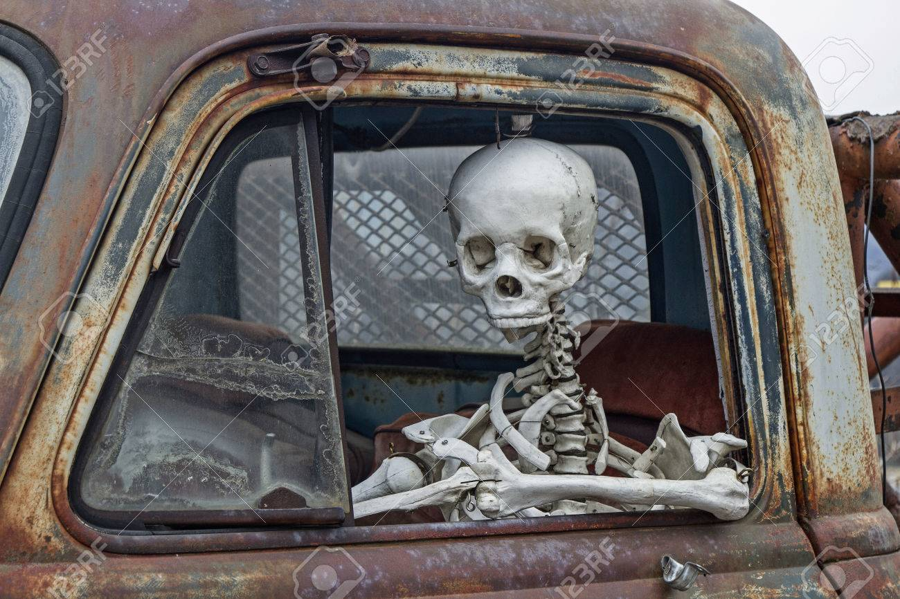 Skeleton At The Wheel Of An Old Junk Cars Stock Photo, Picture And ...