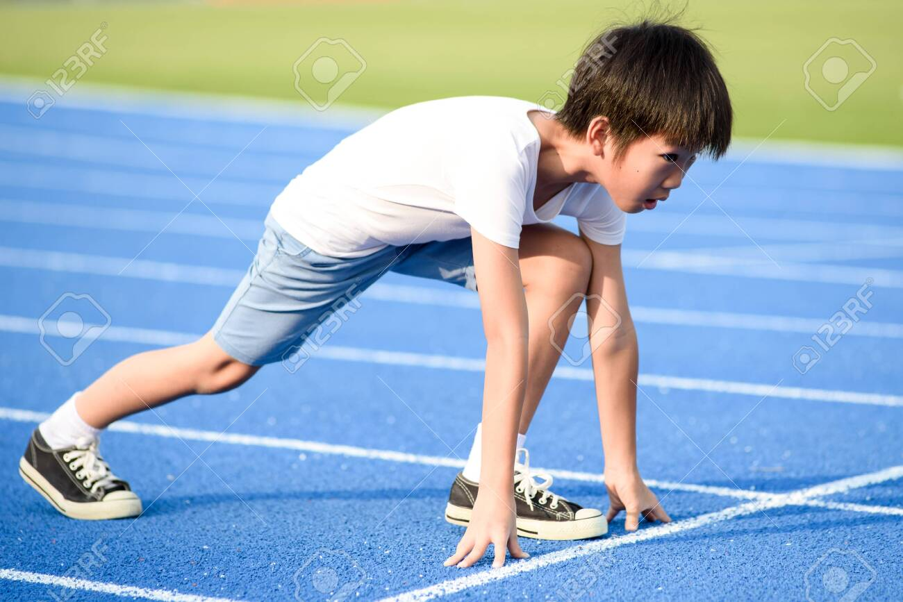 Young Asian boy prepare to start run on a blue track in summer day - 131666468
