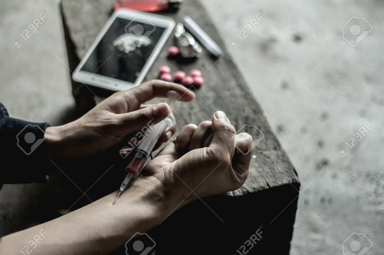 Girl inject heroin injection into blood vessels.The concept of crime and drug addiction. 26 June, International Day Against Drug Abuse and Illicit Trafficking - 105980947