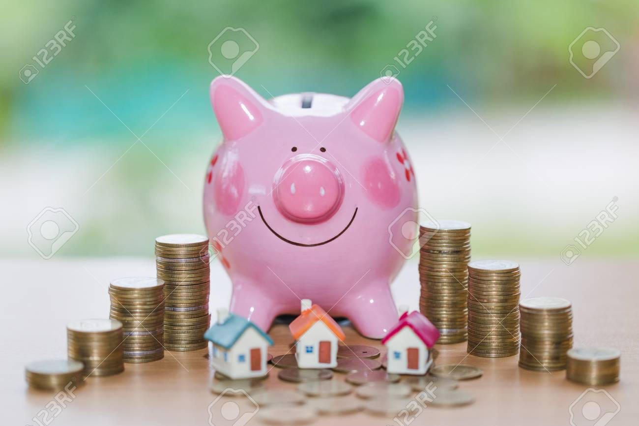 Real estate sale, home savings, piggy bank, coins and a house,