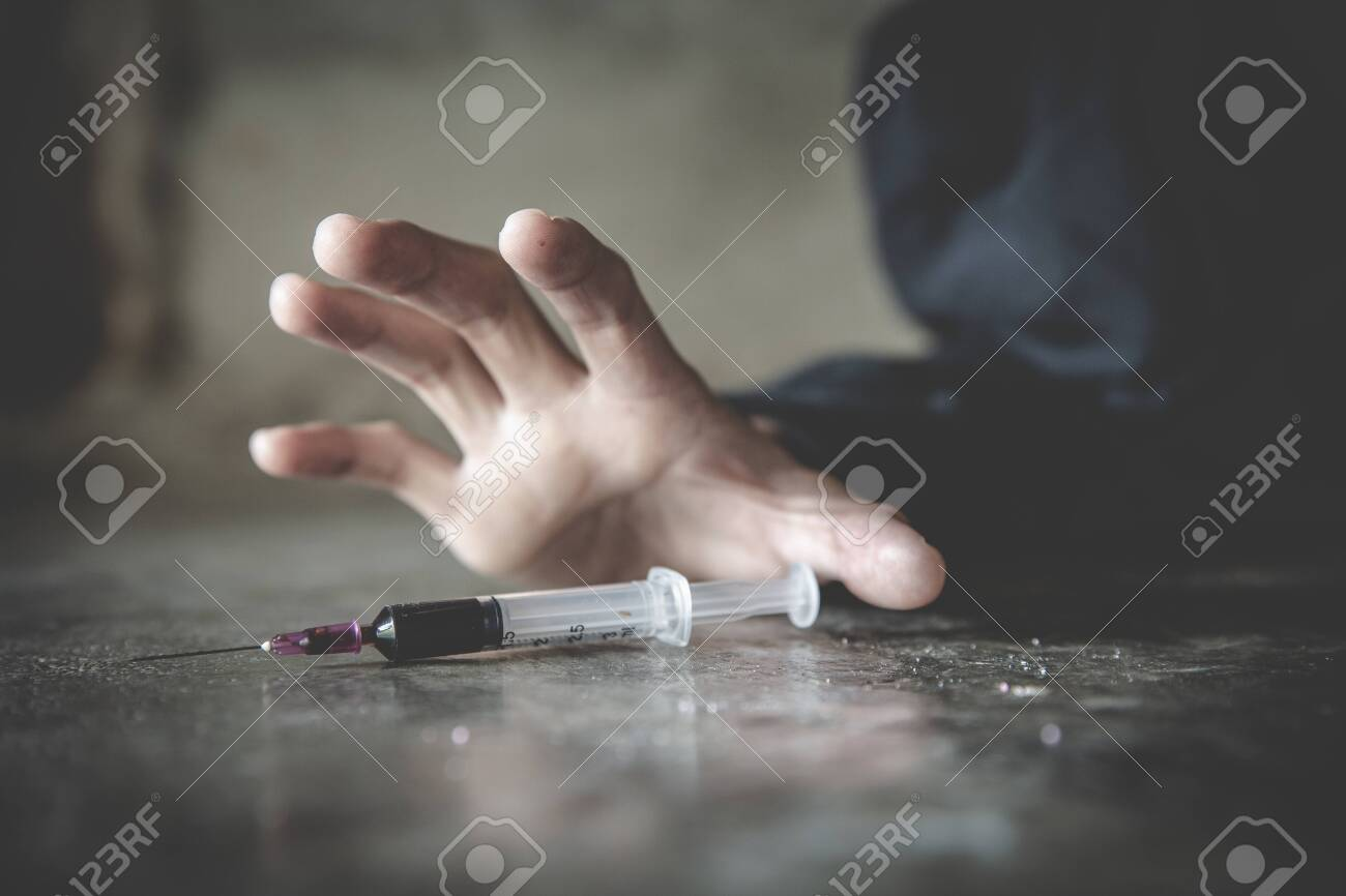 Human hand of a drug addict and a syringe with narcotic syringe lying on the floor, Drug addiction, Anti drug concept. - 134582085