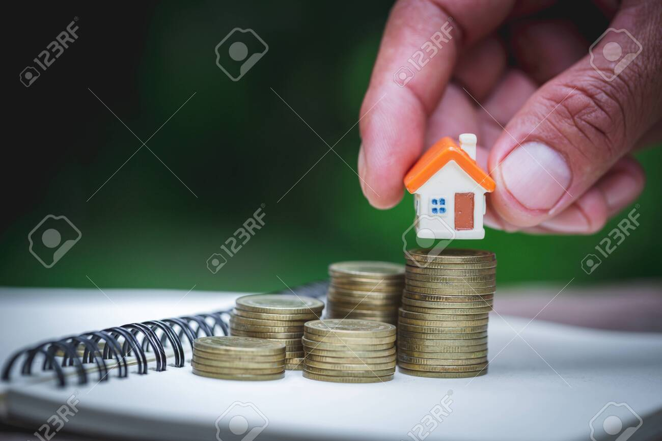 Woman's hand putting house model on coins stack. Concept for property ladder, planning savings money of coins to buy a home concept property mortgage and investment for a house. - 157992019