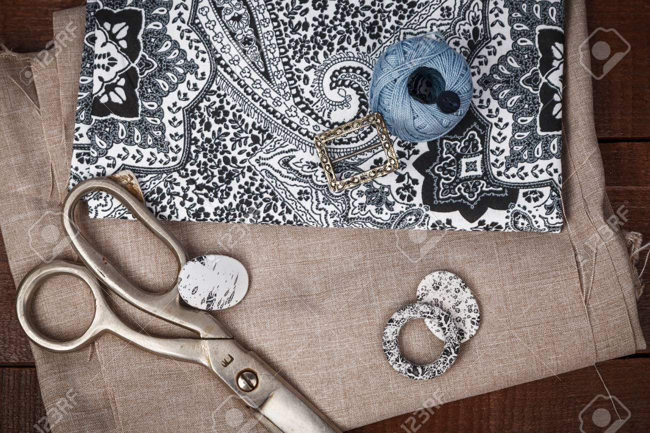 Scissors and buttons on grey pattern fabric, sewing tools and