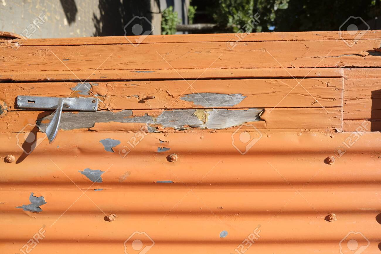 old orange wooden bench with peeling paint - 144082434