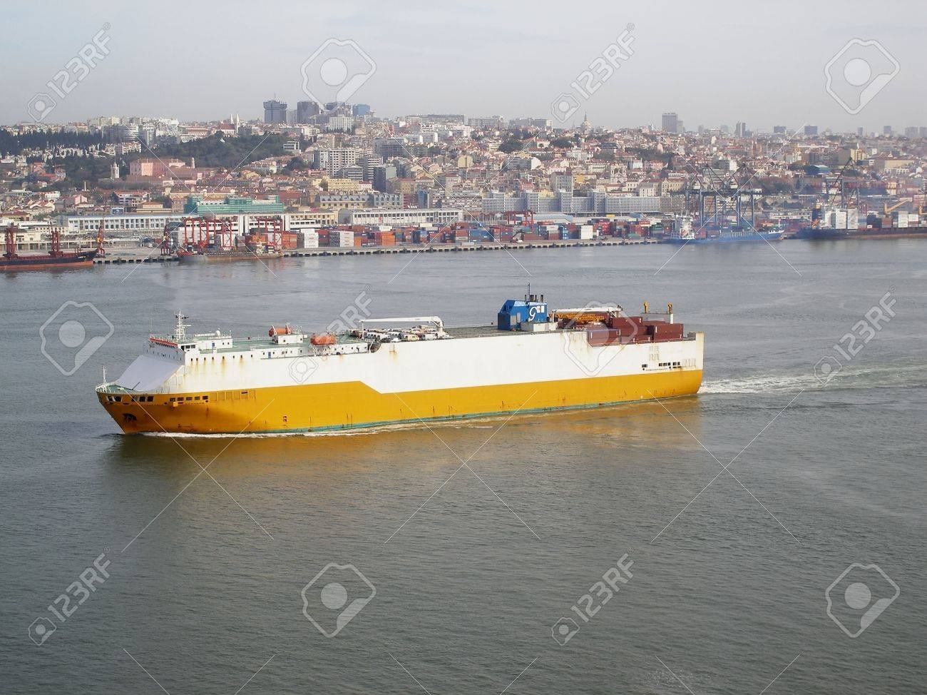 cargo ship navigating with city behind Stock Photo - 404192