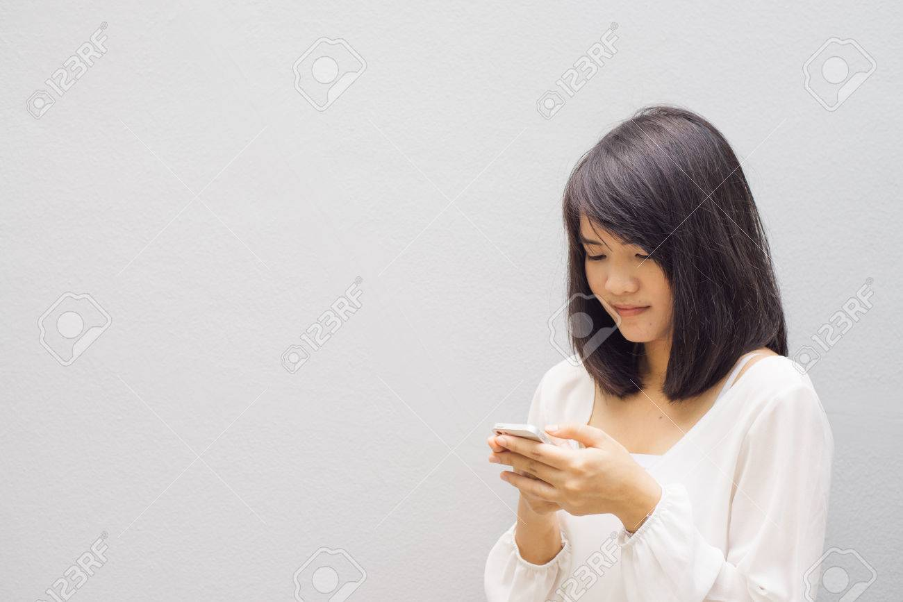 beautiful asian woman using cellphone, over concrete wall - 43655033