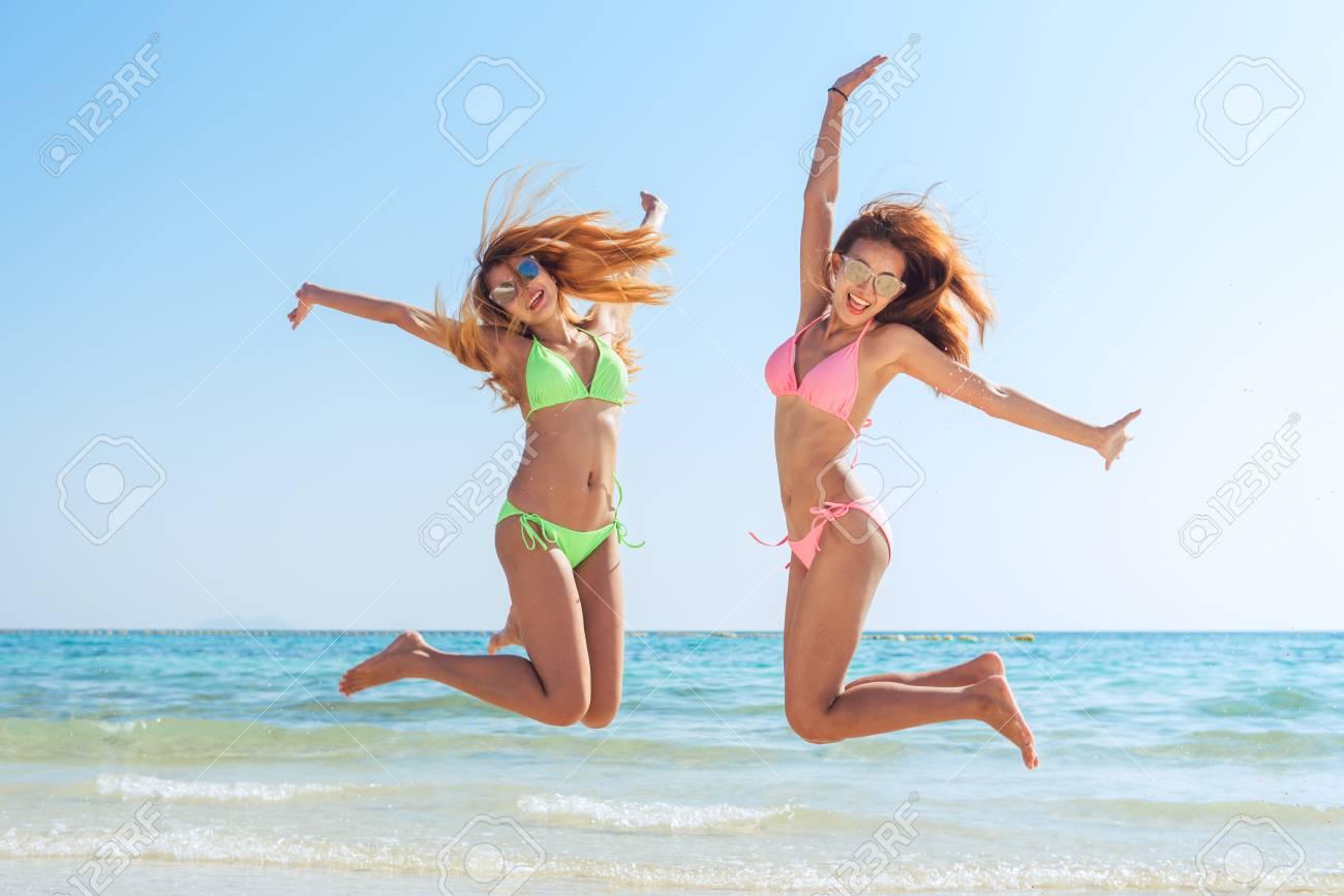 153e4f1882438 Happy bikini two asian women jumping of joy and success on perfect white  sand beach on